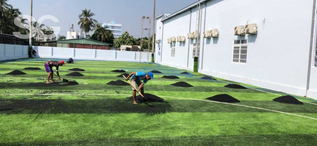 Giai đoạn rải hạt cao su trên bề mặt sân cỏ nhân tạo